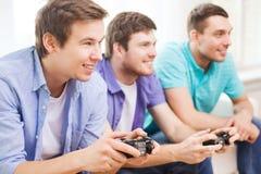 Amigos sonrientes que juegan a los videojuegos en casa Fotografía de archivo
