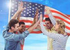Amigos sonrientes que lanzan para arriba sus manos contra fondo de la bandera americana que agita fotos de archivo