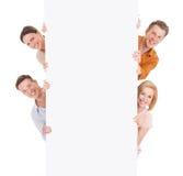 Amigos sonrientes que miran de detrás la cartelera en blanco Imagen de archivo