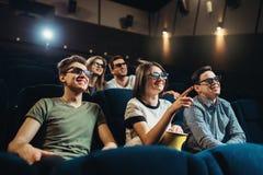 Amigos sonrientes que miran la película 3d en cine Foto de archivo libre de regalías