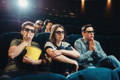 Amigos sonrientes que miran la película 3d en cine Fotos de archivo