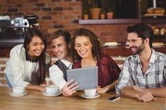 Amigos sonrientes que miran la tableta digital Foto de archivo libre de regalías