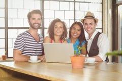 Amigos sonrientes que se colocan alrededor del ordenador portátil Imágenes de archivo libres de regalías