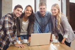 Amigos sonrientes que se colocan alrededor del ordenador portátil Fotos de archivo