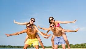 Amigos sonrientes que se divierten en la playa del verano Imagenes de archivo