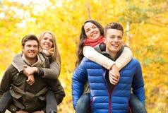 Amigos sonrientes que se divierten en parque del otoño Foto de archivo libre de regalías