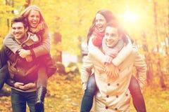 Amigos sonrientes que se divierten en parque del otoño Fotos de archivo libres de regalías