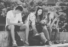 Amigos sonrientes que se sientan con los teléfonos móviles en parque Fotos de archivo libres de regalías