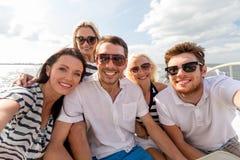 Amigos sonrientes que se sientan en cubierta del yate Imagen de archivo