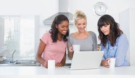 Amigos sonrientes que tienen café junto y mirada del ordenador portátil Foto de archivo libre de regalías