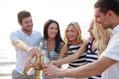 Amigos sonrientes que tintinean las botellas en la playa Fotografía de archivo