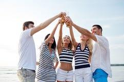 Amigos sonrientes que tintinean las botellas en la playa Imagen de archivo libre de regalías