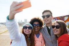 Amigos sonrientes que toman el selfie con smartphone Imagen de archivo libre de regalías