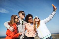 Amigos sonrientes que toman el selfie con smartphone Imágenes de archivo libres de regalías