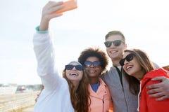 Amigos sonrientes que toman el selfie con smartphone Foto de archivo libre de regalías