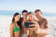 Amigos sonrientes que toman imágenes de ellos mismos Imágenes de archivo libres de regalías