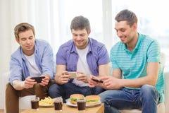 Amigos sonrientes que toman la imagen de la comida en casa Imagenes de archivo