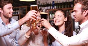 Amigos sonrientes que tuestan así como el vino y la cerveza almacen de video