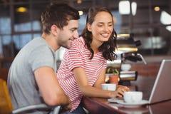 Amigos sonrientes que usan el ordenador portátil y comiendo café junto Foto de archivo libre de regalías