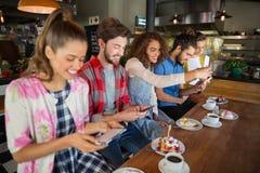 Amigos sonrientes que usan sus teléfonos móviles en restaurante Imagen de archivo