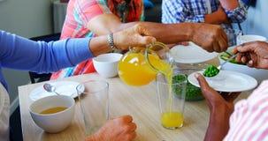 Amigos superiores que comem o café da manhã na mesa de jantar 4k video estoque