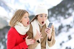 Amigos surpreendidos com um telefone esperto no inverno Fotografia de Stock