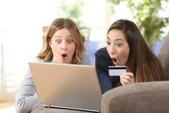 Amigos surpreendidos que compram em linha junto em casa Imagens de Stock Royalty Free