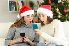 Amigos surpreendidos que encontram ofertas em linha no Natal fotos de stock
