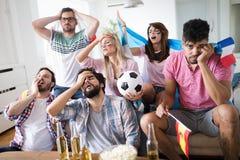 Amigos trastornados que miran el partido de fútbol fotografía de archivo libre de regalías