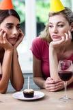 Amigos tristes que sentam-se na tabela durante a festa de anos imagens de stock