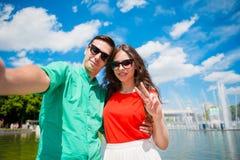 Amigos turísticos jovenes que viajan el días de fiesta en la sonrisa de Europa feliz Muchacha caucásica y hombre que hacen el fon Foto de archivo libre de regalías
