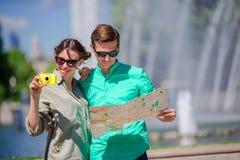 Amigos turísticos jovenes que viajan el días de fiesta en la sonrisa de Europa feliz Muchacha que toma las fotos en el parque y e Fotografía de archivo libre de regalías