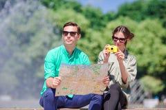 Amigos turísticos jovenes que viajan el días de fiesta en la sonrisa de Europa feliz Pares caucásicos con el mapa de la ciudad en Foto de archivo libre de regalías
