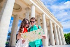 Amigos turísticos jovenes que viajan el días de fiesta en la sonrisa de Europa feliz Familia caucásica con el mapa de la ciudad e Foto de archivo libre de regalías