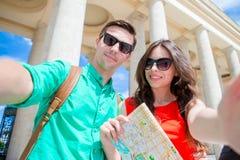 Amigos turísticos jovenes que viajan el días de fiesta en la sonrisa de Europa feliz Familia caucásica con el mapa de la ciudad q Fotos de archivo