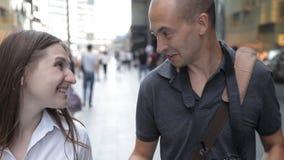 Amigos, um homem e uma mulher, andando ao longo de uma rua movimentada no centro da cidade e falando, sorrindo filme