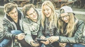 Amigos urbanos novos que têm o divertimento que usa junto o telefone esperto móvel Imagem de Stock Royalty Free