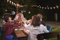 Amigos y familia que hacen una tostada en el partido de cena en jardín imágenes de archivo libres de regalías