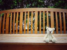 amigurumi crochet teddy bear on bench lonely. Royalty Free Stock Photos