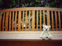 Amigurumi crochet teddy bear on bench lonely. Royalty Free Stock Photos