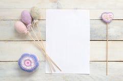 Amigurumi inspirerande vitt kort med någon handgjord garnering för virkning Arkivfoton
