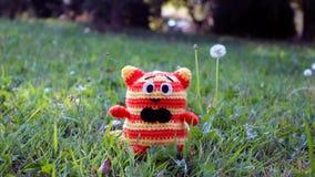 Amigurumi katt på gräs Fotografering för Bildbyråer