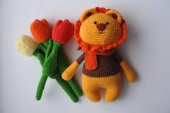 Amigurumi-Spielzeug Löwe mit Tulpen stockfotografie