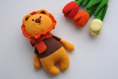 Amigurumi toy. Lion with tulips. Lion toy knitted in the technique of knitting amigurumi Stock Photos