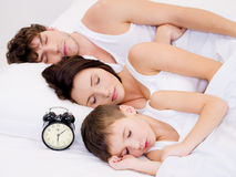 Amily, das mit Alarmuhr nahe ihren Köpfen schläft Stockbilder