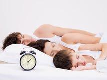 Amily que duerme con el reloj de alarma cerca de sus cabezas imagenes de archivo