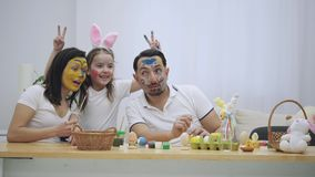 Amily se está sentando en la tabla, llena de decoraciones de Pascua y está mostrando diversas emociones De felicidad a los sadnes