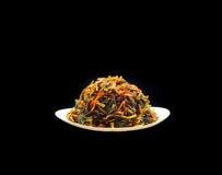Amincissant la salade d'algue du plat blanc d'isolement sur le noir Image stock