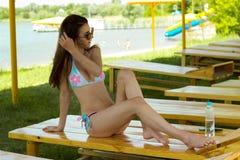 Amincissez la belle brune dans un maillot de bain et des lunettes de soleil sur la plage Photographie stock libre de droits