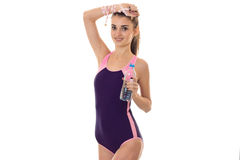 Amincissez la belle dame dans le maillot de bain de corps regardant l'appareil-photo et souriant avec la bouteille de l'eau dans  Images stock